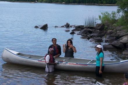 Group cleaning canoe after trip
