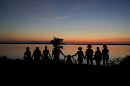 Sunset group holding hands